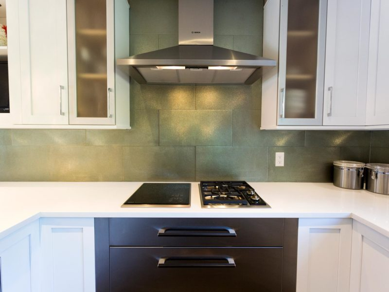 Open and functional trendy Tulsa kitchen design with side-by-side Bosch two burner induction and gas cooktops, warming drawers, Bosch stainless vent hood, glass tile backsplash and wall cabinet storage