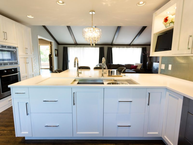 Open and functional trendy Tulsa kitchen remodel, peninsula, Caesarstone quartz counter-top, Galley Workstation stainless kitchen sink, white base cabinet storage and wood floors