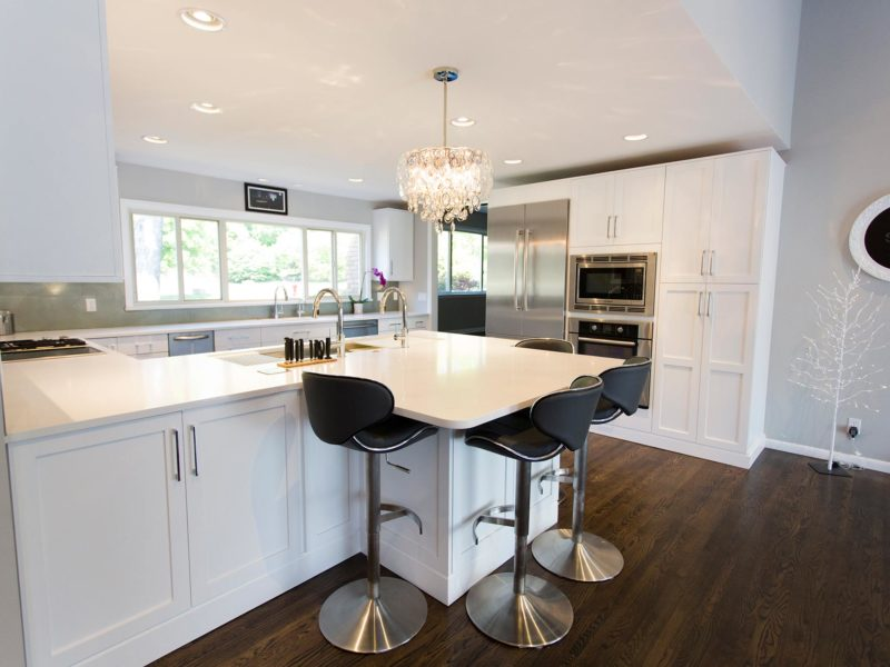 Open and functional trendy Tulsa kitchen remodel with white base cabinet full height peninsula storage with seating space, Bosch cooking, refrigeration, tall pantry storage and wood floors