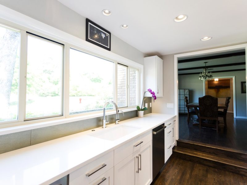 Open and functional trendy Tulsa kitchen remodel with white Blanco clean-up sink, Caesarstone counter-top, formal dining room entry and wood floors