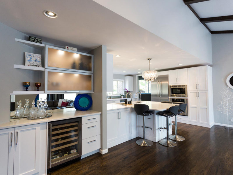Open and functional trendy Tulsa kitchen remodel, white cabinets, stainless wine refrigerator in beverage center, frosted glass cabinets, mirror backsplash and wood floors