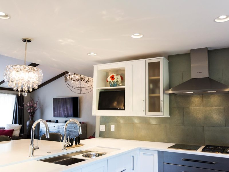 Open and functional trendy Tulsa kitchen with white cabinets, Galley Workstation, Caesarstone quartz counter-top, wall cabinet storage, Bosch cooking appliances and glass tile backsplash