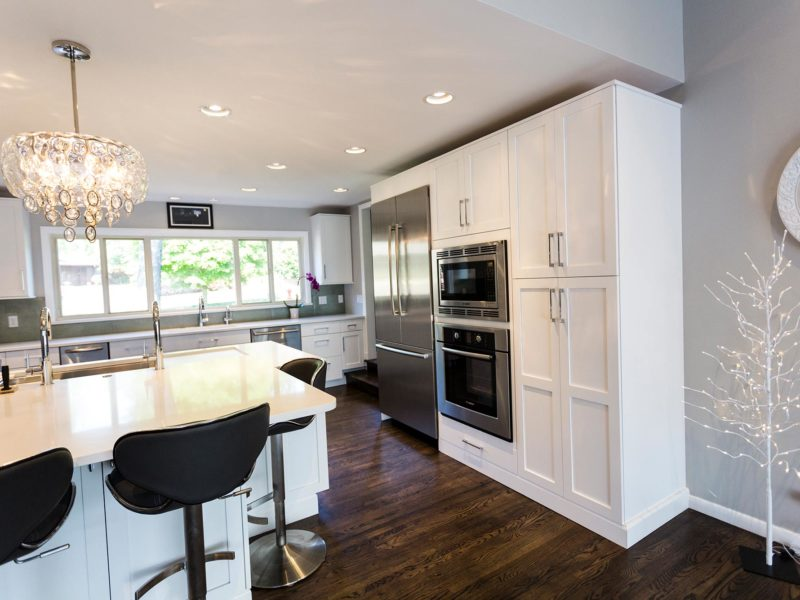 Open and functional Tulsa kitchen design and remodel with white tall cabinet storage, stainless Bosch refrigeration and cooking appliances and wood flooring