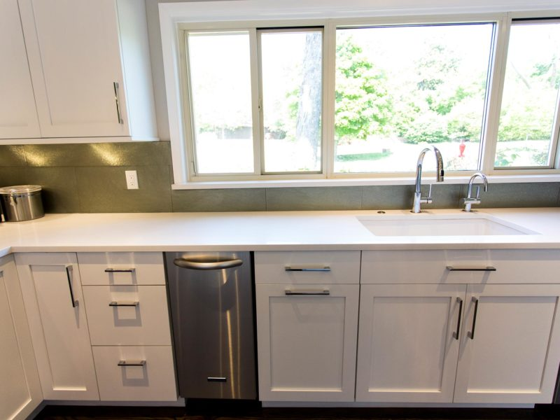 Open and functional Tulsa kitchen with white Blanco clean-up sink, stainless under counter Bosch ice maker, dishwasher, white base cabinet storage and glass tile backsplash