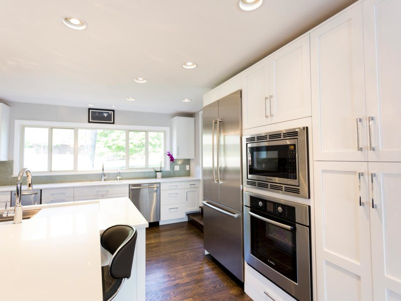 Open and functional Tulsa kitchen with white cabinets, quartz counter-tops, stainless, Bosch tall refrigerator/freezer, microwave, oven and tall pantry storage