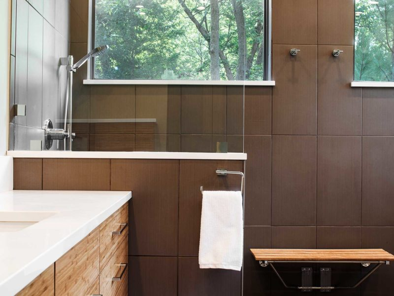 Open contemporary Tulsa master bath design and remodel with walk-in shower, wood bench seating, medium brown wood grain base vanity storage, quartz counter-tops and glass partition
