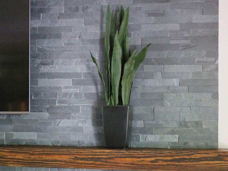 Open remodeled Tulsa living room staggered stone backsplash wood fireplace mantle