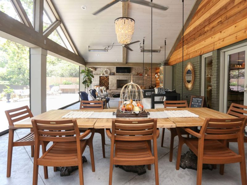 Open spacious Tulsa patio design and remodel with dining table, outdoor seating and stone wood burning fireplace