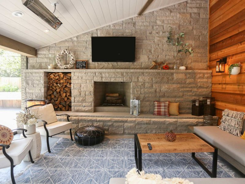 Spacious open Tulsa patio design and remodel living space with stone wood burning fireplace, concrete flooring and vaulted ceiling with wood paneling.