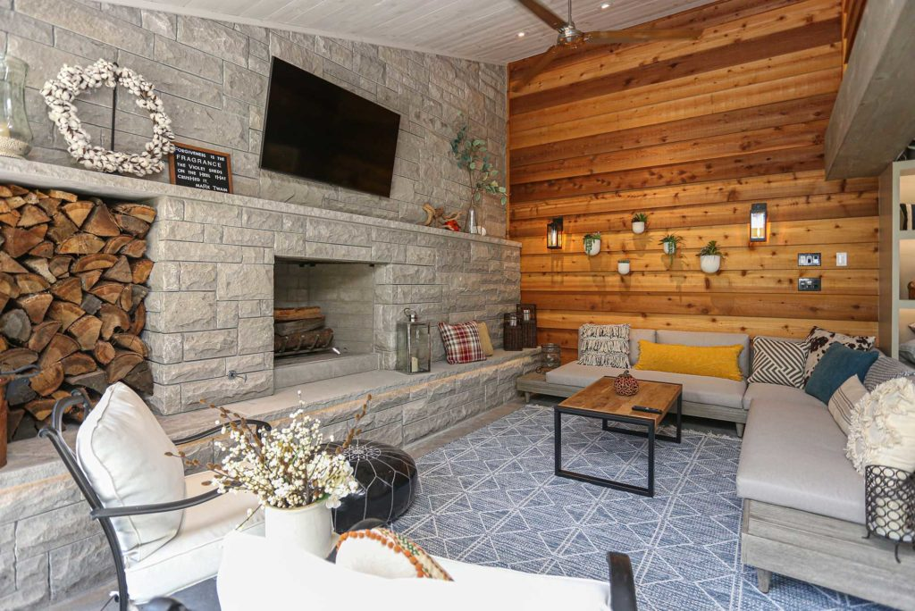 Beautiful Tulsa patio design and remodel with stone wood burning fireplace, wall mounted television, wood paneling, concrete flooring and outdoor furniture