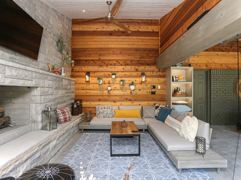 Open spacious Tulsa patio design and remodel with stone wood burning fireplace, wall mounted television, wood paneling and outdoor furniture