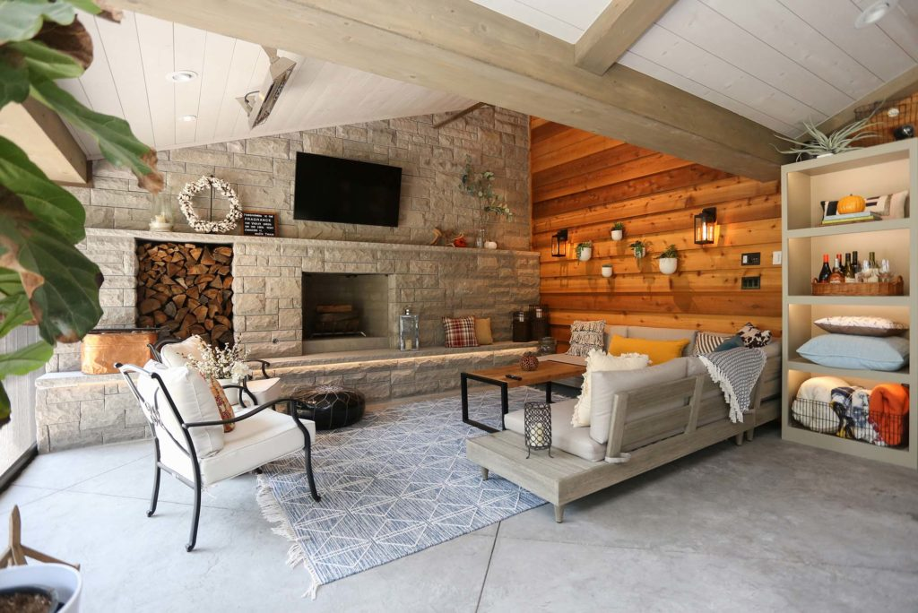 Spacious open Tulsa patio design and remodel living space with stone wood burning fireplace, concrete flooring and vaulted ceiling with wood paneling
