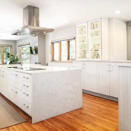Open transitional white Tulsa kitchen design and remodel, Bosch stainless professional vent hood, island with waterfall edge counter, Bosch induction cooktop, Galley Workstation and wood floors
