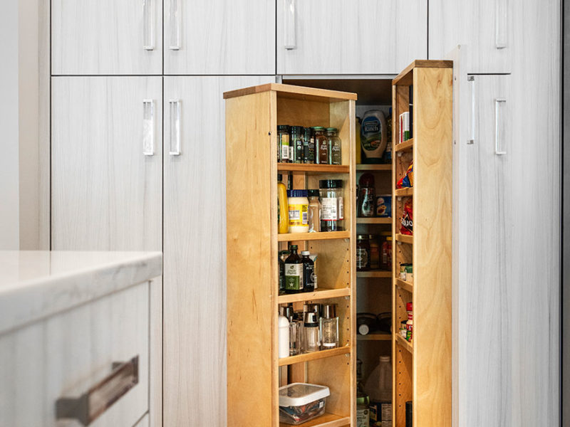 Open transitional white Tulsa kitchen design and remodel with tall pantry storage featuring clear hardware for condiments and dry food goods storage and wood flooring