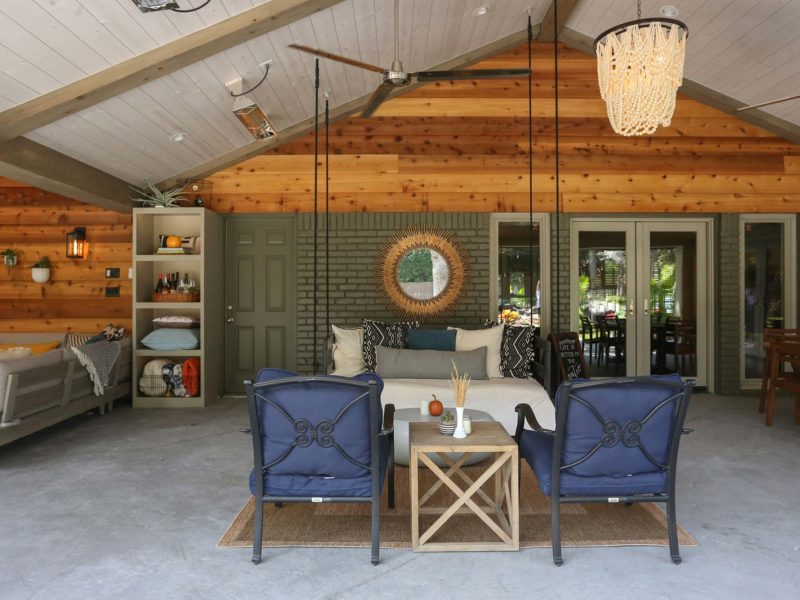 Open spacious Tulsa patio design and remodel living area with bench swing, concrete flooring and vaulted ceiling with wood paneling