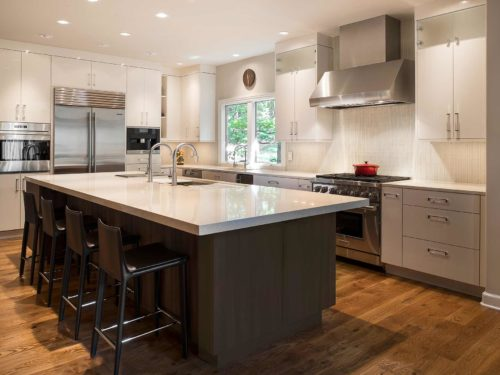 Spacious modern functional Tulsa kitchen remodel with large island dark cabinets, quartz counter-top, white perimeter cabinets, professional Sub-Zero Wolf, Miele coffee and Galley Workstation
