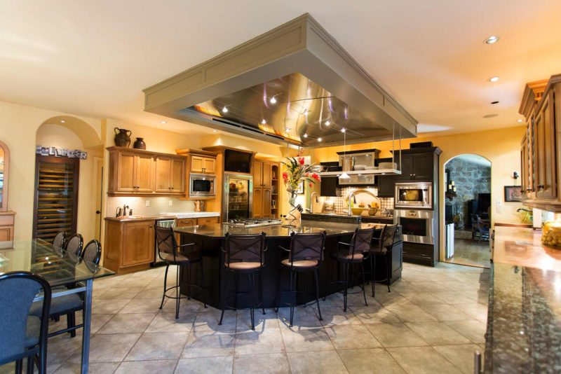 Open classic tuscan style kitchen featuring large island and functioning vent hood.