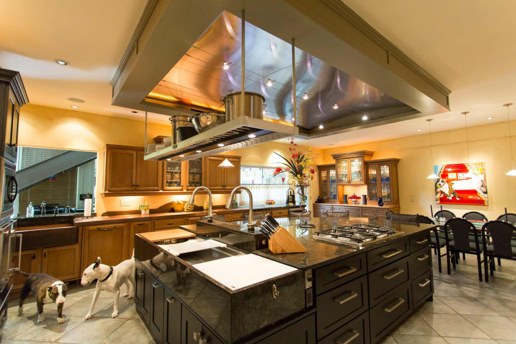 Classic tuscan style kitchen with large island featuring pullout storage, Galley Workstation kitchen sink and functioning vent hood.