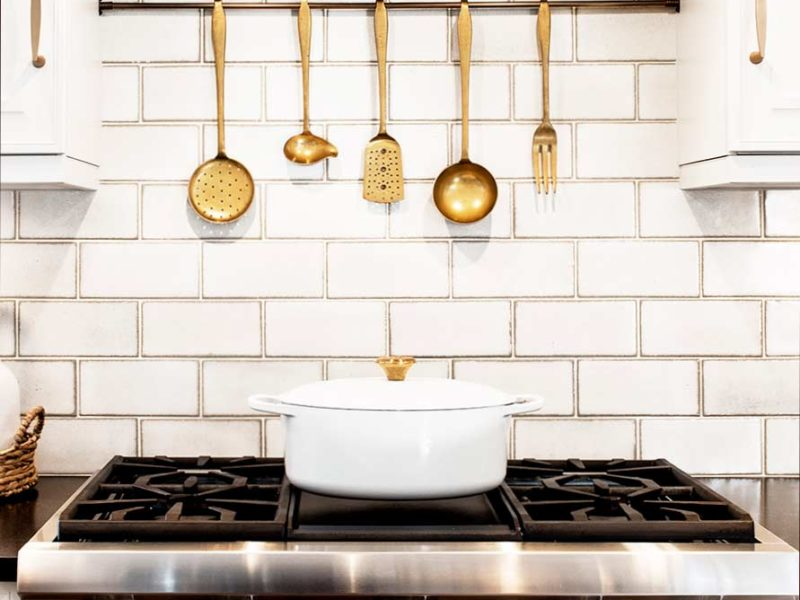Traditional Tulsa kitchen with stainless Thermador professional gas rangetop, vent hood, accented by subway tile backsplash