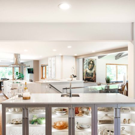 Transitional Tulsa kitchen design and remodel with white cabinets, white marble counters, Bosch professional appliances, lit glass front bar island storage with bar sink and wood floors