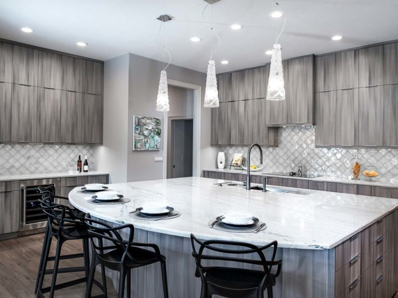 Warm contemporary open Tulsa kitchen remodel with large island Galley Workstation, rich Harmoni cabinetry, refinished wood floors, stainless appliances and decorative ceramic tile backsplash