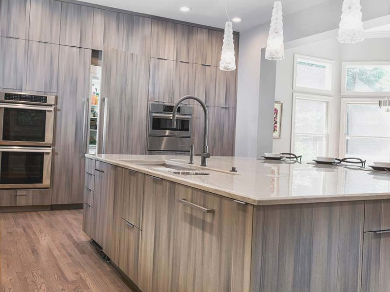 Contemporary open Tulsa kitchen design and remodel with large island storage, Galley Workstation kitchen sink, Harmoni cabinet storage and integrated refrigerator/freezer