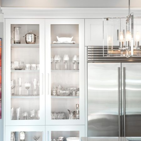 White art deco Tulsa penthouse kitchen design and remodel with tall pantry storage, stainless Sub-Zero refrigerator/freezer