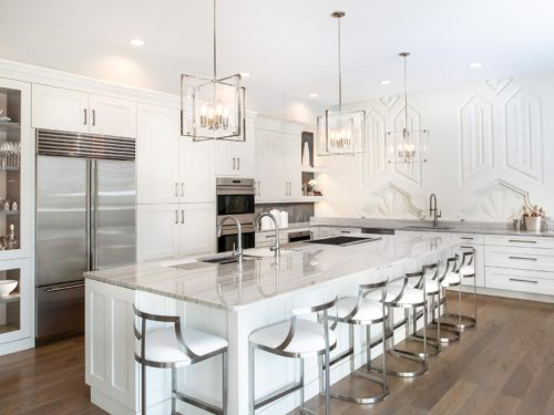 Art deco white Tulsa penthouse kitchen remodel with wood floors, large island, gas cooktop, Galley Workstation, Sub-Zero Wolf appliances, tall pantry storage and clean-up sink