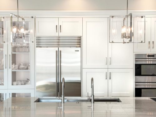 Art deco white Tulsa penthouse kitchen featuring tall pantry storage, stainless Sub-Zero refrigerator freezer, Wolf ovens and Galley Workstation in large island