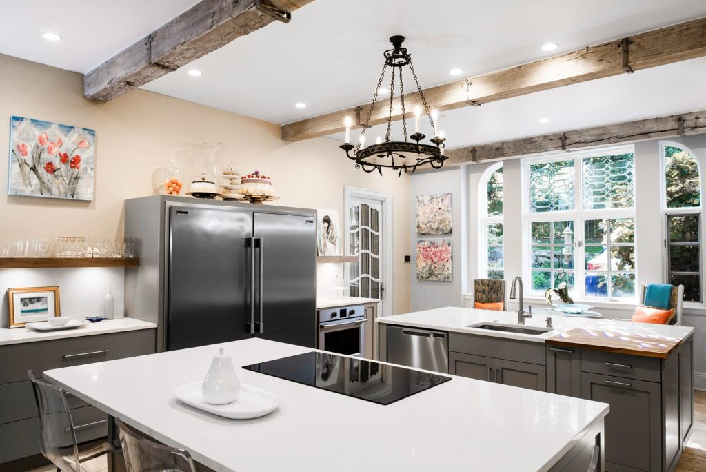 Comfy Tulsa kitchen featuring two islands, induction cooktop, prep sink, stainless dishwasher and floating shelves flanking Frigidaire all freezer/refrigerator with under counter oven below