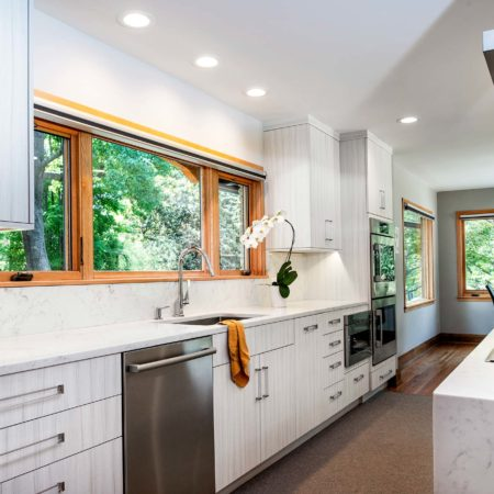 Transitional bright Tulsa kitchen featuring flat panel cabinet doors with cleanup sink, stainless front dishwasher and professional stainless ovens