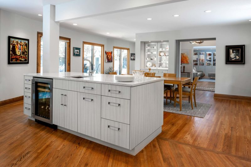 Transitional bright Tulsa kitchen with island bar featuring flat panel cabinet doors, bar sink and stainless under counter wine refrigerator