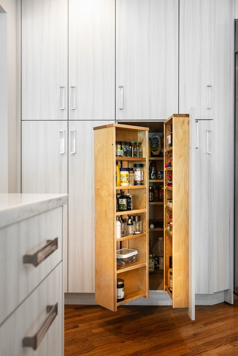 Transitional bright Tulsa kitchen remodel with tall pantry storage featuring plentiful cubbies for condiments, oils, spices and containers