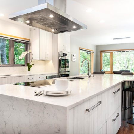 Beautiful Rock Star transitional bright Tulsa kitchen with stainless professional hood over island featuring waterfall counter top edge, induction cooktop and seating area