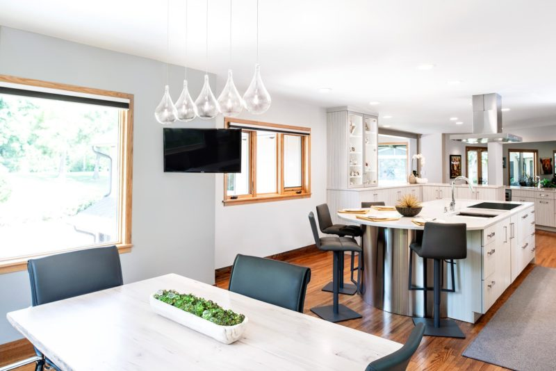 Beautiful Rock Star transitional bright Tulsa kitchen with island housing induction cooktop, sink and seating area with counter top level wall cabinet