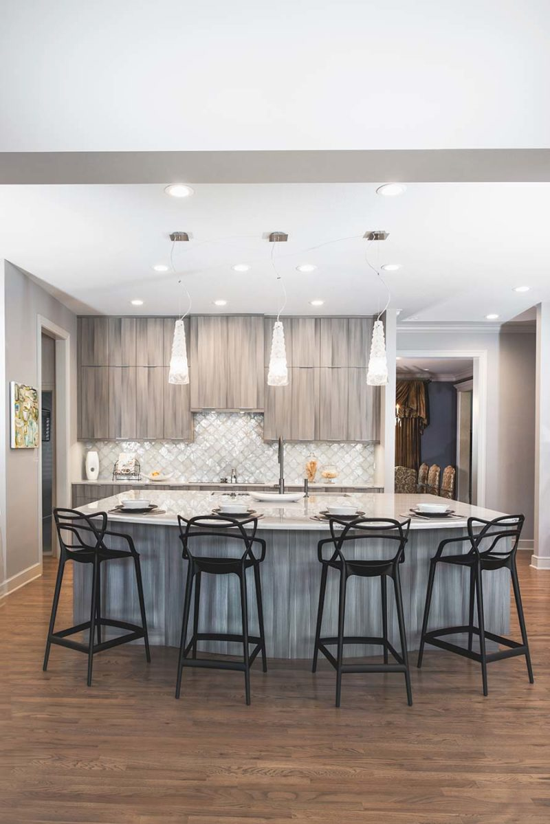 Culinary Elegance 2 warm transitional open kitchen with large island featuring Galley Workstation, beautiful Harmoni cabinets, wood floors and stainless appliances
