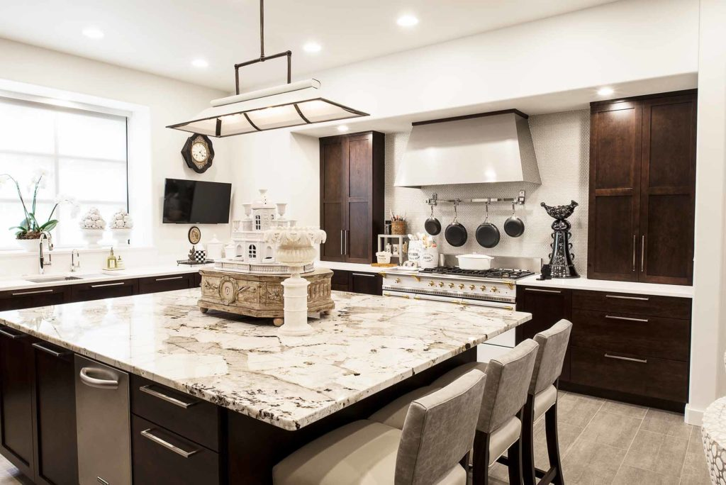 Tulsa kitchen featuring large island with marble counter top, seating, rich brown base cabinet storage, designer pendant lighting and Lacanche french range.