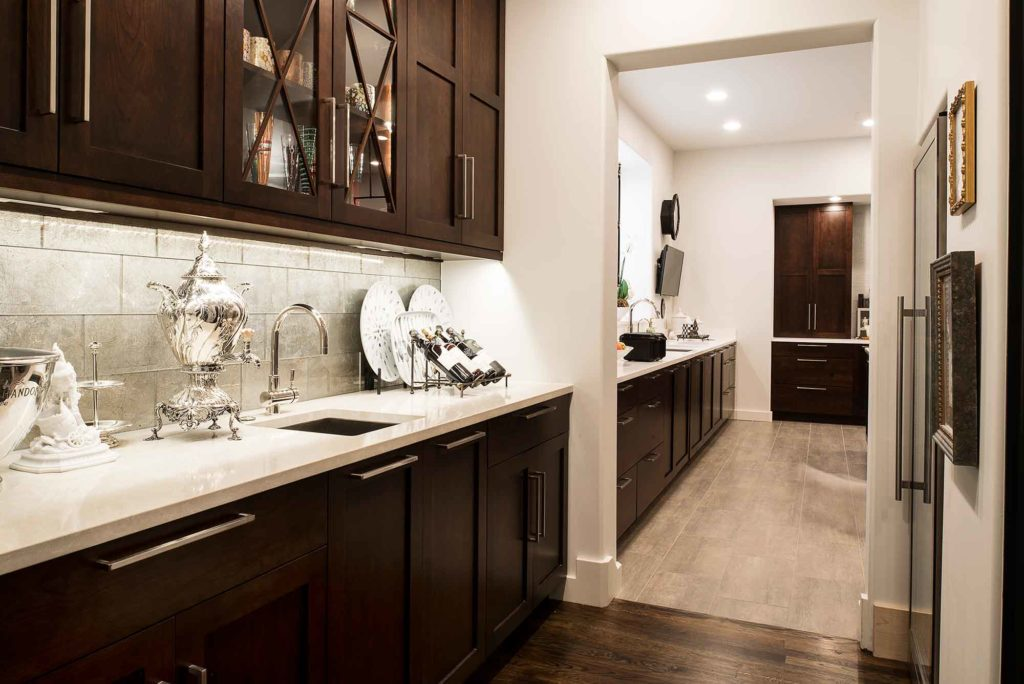 Classy Tulsa kitchen with adjoining bar space featuring decorative tile backsplash, wall cabinet cook book storage and bar sink.