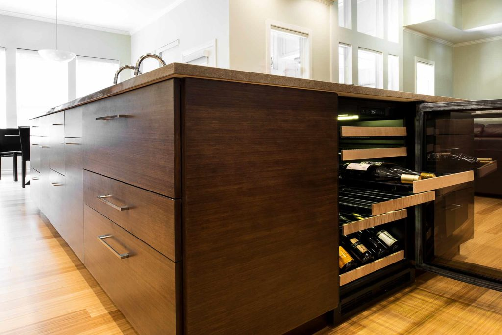 Contemporary Tulsa kitchen with large bamboo cabinet island including stainless under-counter wine refrigerator and wood flooring.
