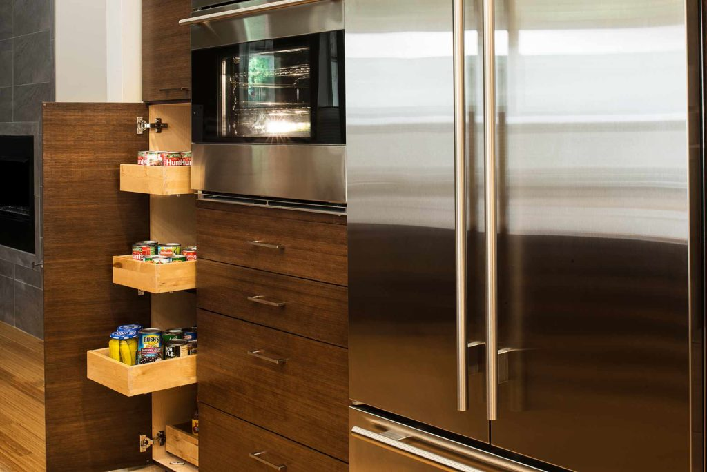 Contemporary Tulsa kitchen designed with bamboo tall pantry pull-out storage cabinetry, stainless convection microwave and full size stainless freezer/refrigerator.