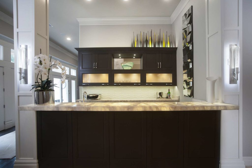 Contemporary stylish open bar area with lit frosted glass cabinet storage and bar sink in the peninsula