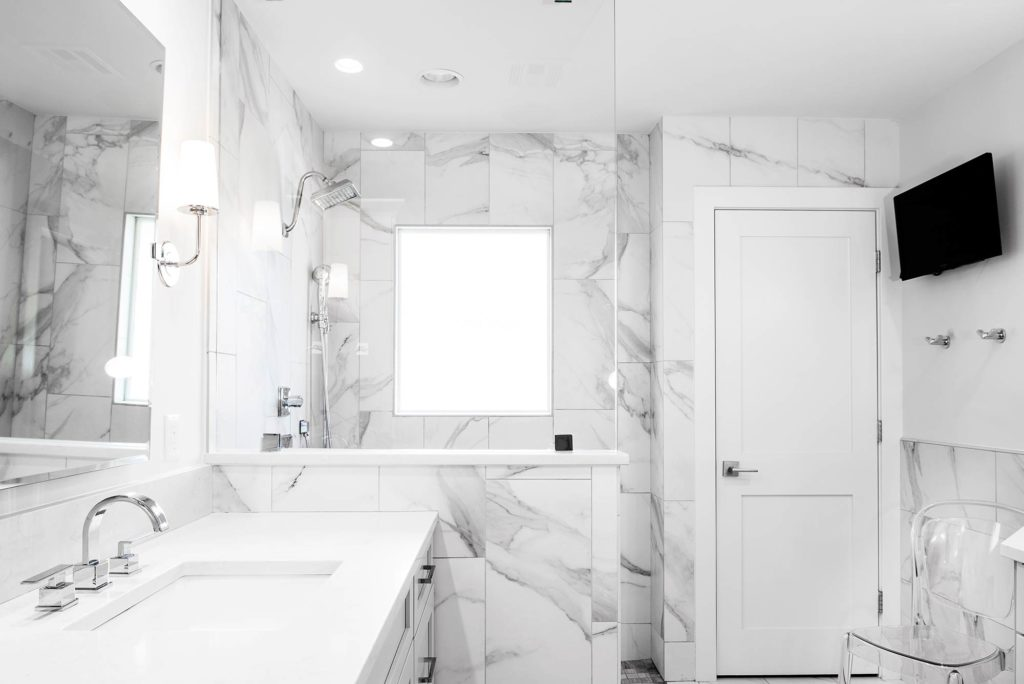 Modern fresh white Tulsa master bathroom remodel designed with vanity space and walk-in shower covered with decorative tile