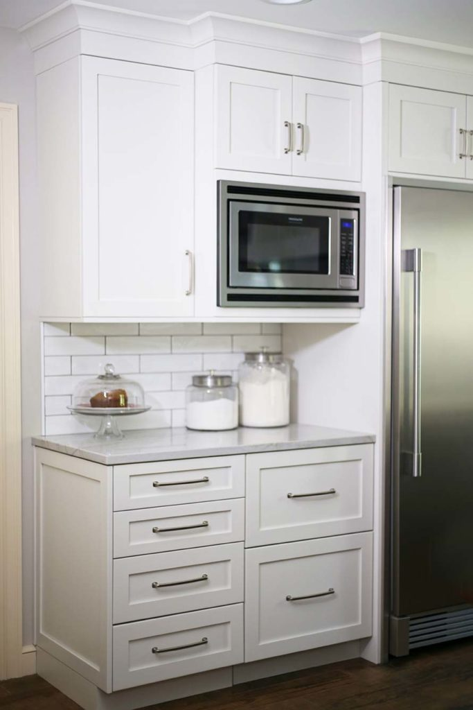 Spacious Tulsa kitchen including Frigidaire microwave, Sub-Zero stainless refrigerator/freezer and panel front drawer refrigerator surrounded by white shaker cabinets