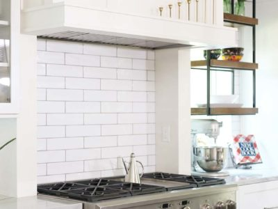 Spacious Tulsa kitchen with GE Cafe gas range and decorative vent hood and white subway tile backsplash with open shelves and shaker cabinet drawer storage