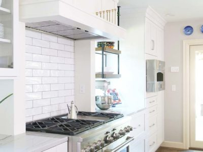 Spacious Tulsa kitchen remodel with GE Cafe gas range, decorative vent hood, subway tile backsplash, GE Monogram hearth oven and large ceiling height crown molding