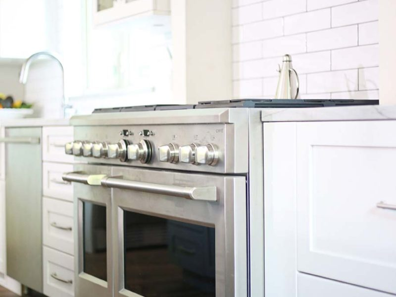Spacious Tulsa kitchen remodel with GE Cafe gas range and vent hood above backed by subway tile backsplash