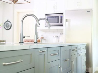 Tulsa kitchen remodel with blue/gray shaker cabinet storage in the large island below a Galley Workstation and decorate pedant lighting