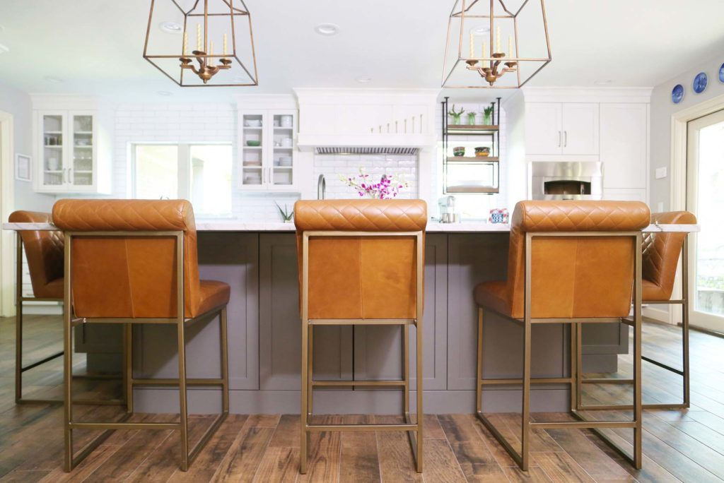 Spacious Tulsa kitchen remodel with large kitchen island, stylish orange leather seating and decorative island pendant lights above.