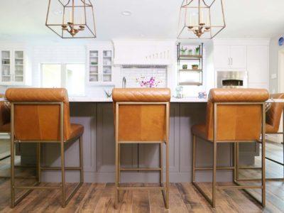 Spacious Tulsa kitchen remodel with large kitchen island, stylish orange leather seating and decorative island pendant lights above.