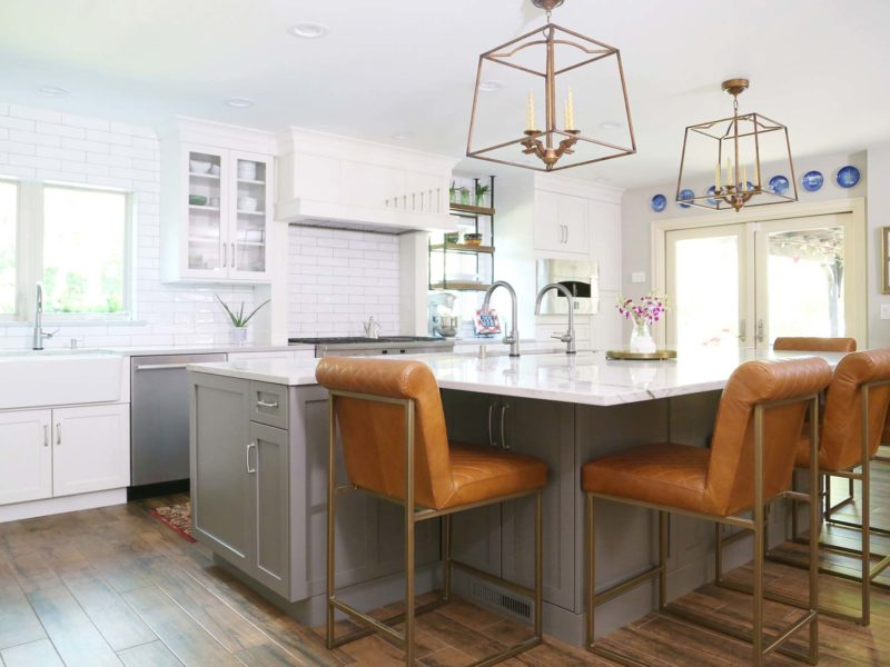 Spacious open Tulsa kitchen with white shaker perimeter cabinets and gray shaker island cabinet storage, white marble counters, leather seating and luxury vinyl wood flooring